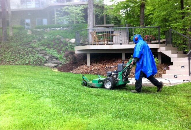 man lawn mowing in the rain